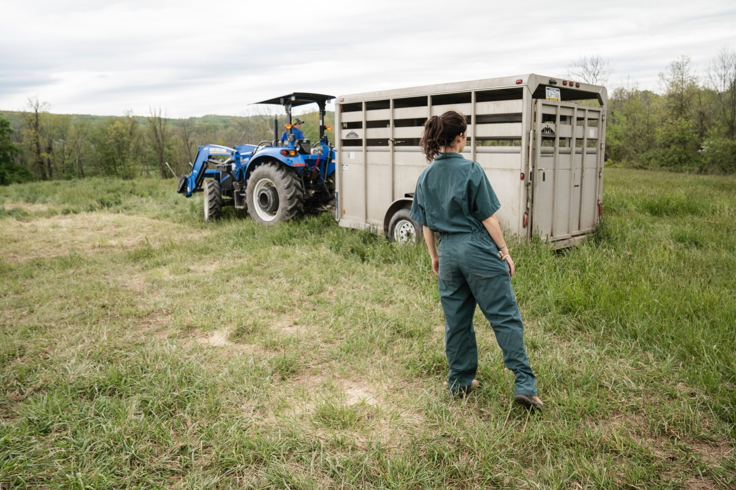 man in blue denim jeans standing beside blue tractor during daytime